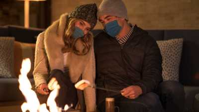 Couple with masks snuggling and roasting marshmallows at fire pit.